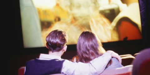 Teenage couple (16-17) sitting in cinema, watching movie