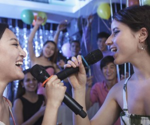 Two friends singing together at karaoke