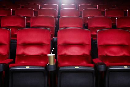 Rote Sitze in einem Kinosaal mit einem Getränk