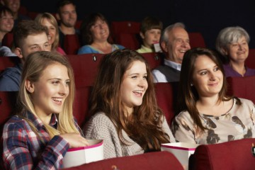 Group Of Teenage Girls Watching Film In Cinema
